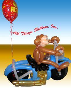 balloon decor: balloon monkey on balloon motorcycle for adult birthday event